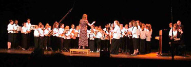 Picture of Wendy Marks conducting a massed recorder group of children at the New Theatre in Oxford